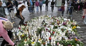 People lay candles and flowers at the makeshift memorial for the victims of Friday's stabbings at the Turku Market Square. Photograph: Lehtikuva/Vesa Moilanen / Getty Images