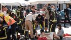 Paramedics tend to one of the many pedestrians struck by a van driving through crowds on Las Ramblas. Photograph: New York Times