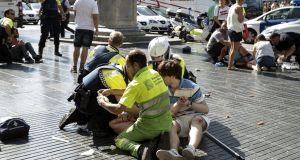 Medics and police tend to injured people near the scene of a terrorist attack in the Las Ramblas area on Thursday. Photograph: Getty