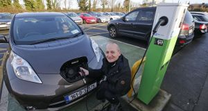 'Irish Times' journalist Justin Comiskey charging his electric car at Booterstown Dart Station. The UK National Grid has warned that charging cars at home could blow main fuses. Photograph: Nick Bradshaw