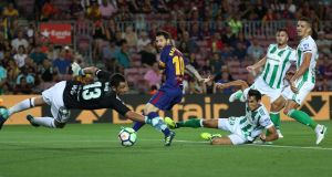 Lionel Messi looks an as Betis defender Alin Tosca scores Barcelona's first goal Photograph: Sergio Perez/Reuters