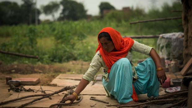 The neighbour: Anjum breaks wood for a cooking fire in Peepli Kera, India. She tried to intervene when Mukesh was beating his wife to death, but others just watched. Photograph: Andrea Bruce/New York Times