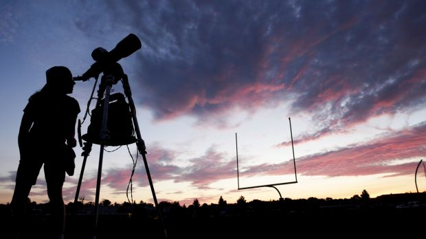 A woman watches through a telescope at Madras High School ahead of a solar eclipse in Madras, Oregon, US. Photograph: Jason Redmond/Reuters