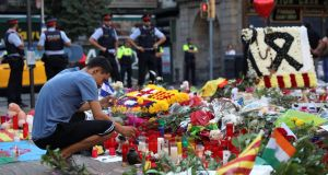 A man lights a candle at an impromptu memorial at Las Ramblas in Barcelona, Spain. Photograph: Reuters/Susana Vera