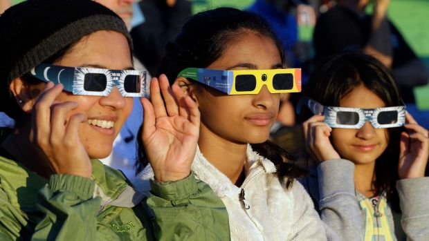From left, Schweta, Rhea and Saanvi Kulkarni, from Seattle, try out eclipse glasses at Salem, Oregon, on Monday, August 21st, 2017. The US was preparing for a total solar eclipse. Photograph: Don Ryan/AP Photo