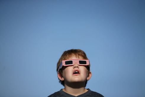 SOLAR ECLIPSE: A boy wears solar-viewing glasses ahead of the solar eclipse, in Depoe Bay, Oregon, US. Photograph: Mike Blake/Reuters