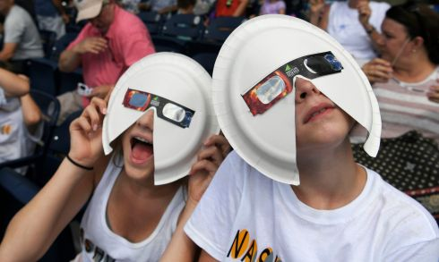 SOLAR ECLIPSE: Annie Gray Penuel and Lauren Peck wear their makeshift eclipse glasses at Nashville's solar eclipse viewing party, in Tennessee, US. Photograph: Shelley Mays/The Tennessean via AP