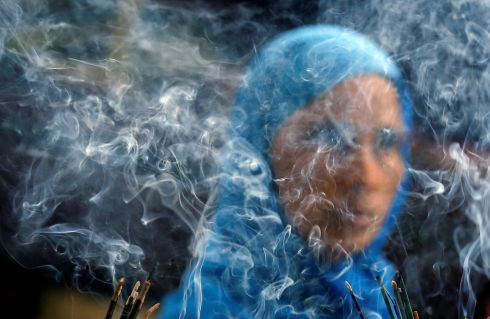 SUFI PRAYER: Smoke rises from burning incense sticks as a woman prays inside the shrine of Muslim Sufi saint Nizamuddin Auliya, in New Delhi, India. Photograph: Adnan Abidi/Reuters