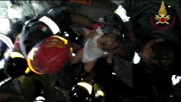 Firefighters saving a seven-month-old baby from rubble after an earthquake on Ischia island, Italy. Photograph: EPA