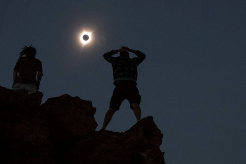Enthusiasts Tanner Person (R) and Josh Blink, both from Vacaville, California, watch a total solar eclipse while standing atop Carroll Rim Trail at Painted Hills, a unit of the John Day Fossil Beds National Monument, near Mitchell, Oregon, U.S. August 21, 2017. Location coordinates for this image is near 44?39'117'' N 120?6'042'' W. REUTERS/Adrees Latif     TPX IMAGES OF THE DAY