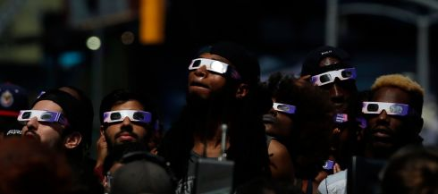 epaselect epa06155407 A group of people look at the solar eclipse from Times Square in New York,  USA, 21 August 2017. The 21 August 2017 total solar eclipse will last a maximum of 2 minutes 43 seconds and the thin path of totality will pass through portions of 14 US states, according to the National Aeronautics and Space Administration (NASA).  EPA/JASON SZENES