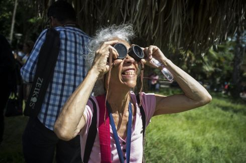 epa06155513 People view the solar eclipse from Caracas, Venezuela, 21 August 2017. The 21 August 2017 total solar eclipse will last a maximum of 2 minutes 43 seconds and the thin path of totality will pass through portions of 14 US states, according to the National Aeronautics and Space Administration (NASA).  EPA/Cristian Hernandez