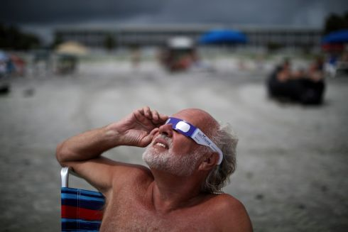 Beachgoers watch the sun enter total eclipse in Folly Beach, S.C., Aug. 21, 2017. For the first time since 1918, a solar eclipse will travel across the entire U.S. on Monday. Millions of people ventured to a spot on the path of totality hoping to catch a glimpse of the rare celestial event. (Travis Dove/The New York Times)