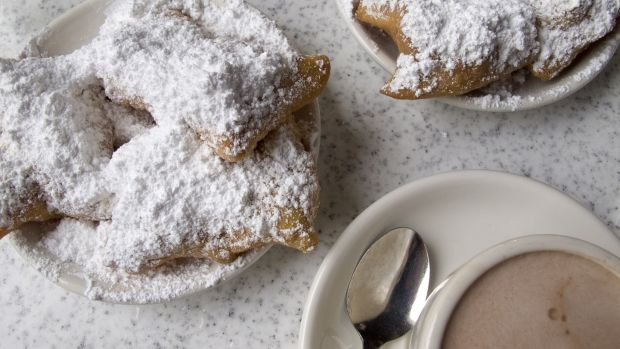 Beignets, a type of fried doughnut, and cafe au lait are popular items at Cafe du Monde, New Orleans