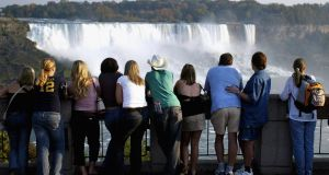 Tourists look out at Niagara Falls from the Canadian side of the Canada/US border. Photograph: Don Emmert/AFP/Getty Images