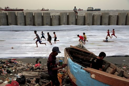 FISHERMAN BLUE: Children play soccer as a fisherman paints his boat near breakwater at Cilincing in Jakarta, Indonesia. Photograph: Beawiharta/Reuters