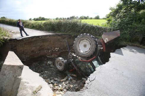 NORTHWEST STORMS: A man looks at a tractor which fell into a river after a road collapsed in Iskaheen, Co Donegal, following heavy rain in the area. Photograph: Niall Carson/PA Wire