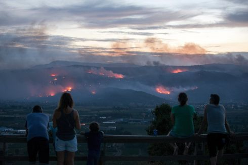 SPANISH FIRE: A group of people watch a forest fire burning in Monterrei, northern Spain. Photograph: Brais Lorenzo/EPA