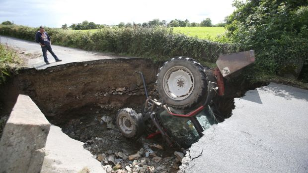 A man looks at a tractor which has fallen into a river after a road collapsed in Iskaheen, Co Donegal after heavy rain left a trail of destruction. Photograph: Niall Carson/PA Wire