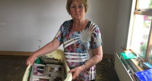 Greta Mooney, who came home on Tuesday to find her bungalow completely flooded, carries a  laundry basket full of framed family photographs. Photogaph: Freya McClements.