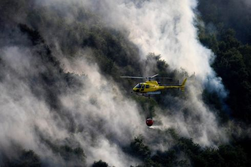 FOREST FIRE: A helicopter drops water over a forest fire in Vilarello, Lugo, northwestern Spain. Photograph:  Eliseo Trigo/EPA