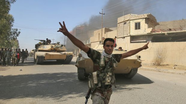 An Iraqi forces fighter celebrates as government forces vehicles move through Tal Afar. Photograph: Ahmad Al-Rubaye/AFP/Getty Images
