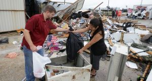 Kenneth Bryant and his wife, Jennifer Bryant, search through debris from Bryant's Auto Sales in Katy, Texas after  Hurricane Harvey passed through. Photograph: Melissa Phillip /Houston Chronicle/AP