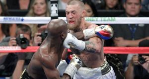 Conor McGregor takes a punch to the face from Floyd Mayweather during their bout in Las Vegas. Photo: John Gurzinski/Getty Images
