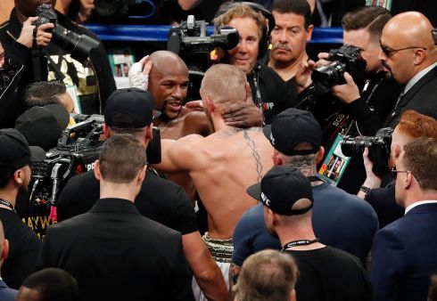 Floyd Mayweather Jr., center left, embraces Conor McGregor after their super welterweight boxing match  in Las Vegas. (AP Photo/Eric Jamison)