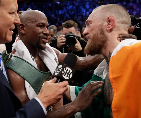 Floyd Mayweather Jr. speaks with Conor McGregor after their boxing match in Las Vegas. (AP Photo/Isaac Brekken)