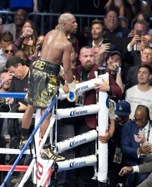 Floyd Mayweather climbs the ring corner ropes to celebrate his victory over Conor McGregor  of Ireland during their fight  in Las Vegas, Photo: EPA/ARMANDO ARORIZO