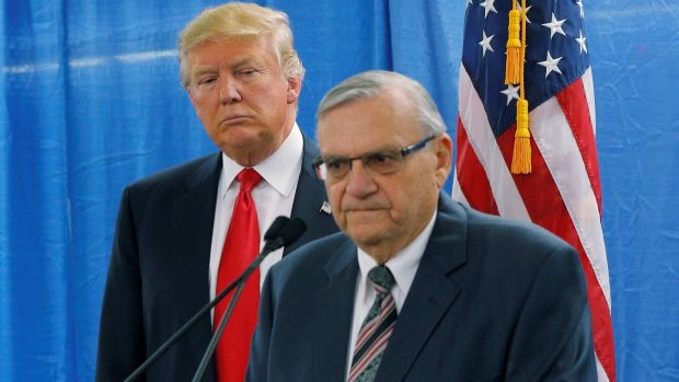 Donald Trump listens as Joe Arpaio (R) speaks to reporters before a campaign rally in Iowa in January. File photograph: Brian Snyder/Reuters