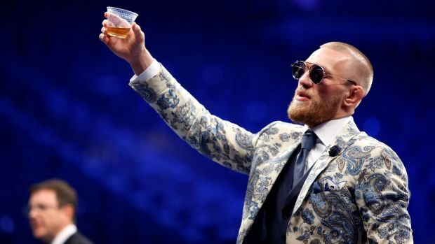 Conor McGregor raises a glass of whiskey during the post-fight news conference. Photograph: Steve Marcus/Reuters