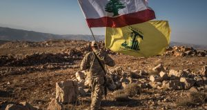 A Hezbollah fighter carries the Hezbollah (top) and Lebanese flags in the Jaroud Arsal area of Lebanon, near the Syrian border in July. File photograph: Sergey Ponomarev/The New York Times