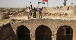 Fighters backing the Iraqi forces pose with the Iraqi flag from Tal Afar's Ottoman-era historic citadel on Sunday. Photograph: Ahmad Al-Rubayeahmad/Getty