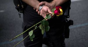 A police officer holds roses during a demonstration against last week's terrorist attacks in Spain. Photograph: David Ramos/Getty Images