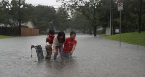 A man helps children across a flooded street as they evacuate their home after the area was inundated with flooding from Hurricane Harvey. Photograph: Getty