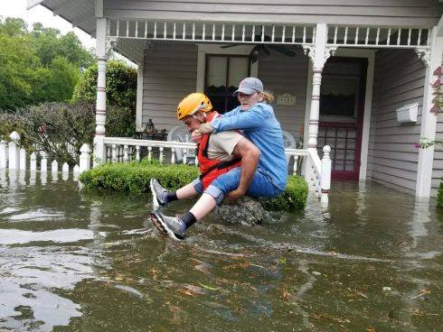 A Texas National Guard soldier carries a woman on his bank as they conduct rescue operations in flooded areas around Houston, Texas, U.S., August 27.   1Lt. Zachary West, 100th MPAD/Texas Military Department/Handout via REUTERS