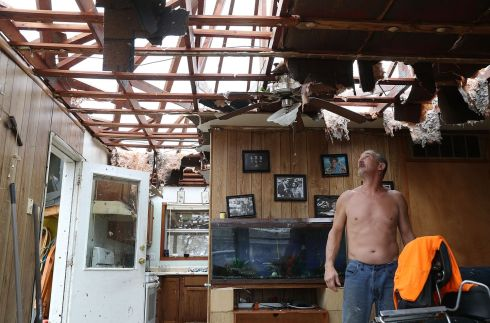 Aaron Tobias who said he lost everything stands in what is left of his home  after Hurricane Harvey blew in and destroyed most of the house on August 26, 2017 in Rockport, Texas. Mr. Tobias said he was able to get his wife and kids out before the storm arrived but he stayed there and rode it out.  (Photo by Joe Raedle/Getty Images)