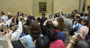 Crowds of tourists attempt to take photographs of the Mona Lisa at the Louvre museum in Paris. Readers found the queues and the small size of the painting to be underwhelming