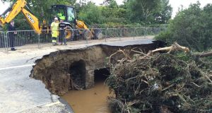 Damage to the main Derry to Moville road in Co Donegal caused by the force of a flooded river overnight, after heavy rain left a trail of destruction. Photograph:  Brian Hutton/PA Wire
