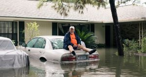 A man sits on a car as flood waters cover the Meyerland neighbourhood of Houston, Texas, US. Photograph: Alyssa Schukar/The New York Times