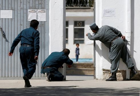 SCARED STIFF: Afghan policemen try to rescue Ali Ahmad (4) at the site of a suicide bombing followed by a clash between Afghan forces and insurgents after an attack on a Shia Muslim mosque in Kabul. Photograph: Omar Sobhani/Reuters