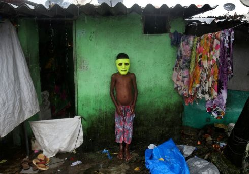 THE MASK: A boy takes shelter from the rain outside his home in a slum in Mumbai, India. Photograph: Shailesh Andrade/Reuters