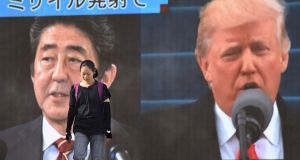A woman walks in front of a huge screen displaying Japanese prime minister Shinzo Abe (L) and  Donald Trump (R) in Tokyo on Tuesday. Photograph: Kazuhiro Nogi/AFP/Getty Images