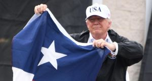 US president Donald Trump holds the state flag of Texas outside of the Annaville Fire House after attending a briefing on Tropical Storm Harvey in Corpus Christi, Texas. Photograph: Jim Watson/AFP/Getty Images