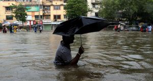 A man wades through a waterlogged street following heavy rains in Mumbai on Tuesday.  Photograph: Rajanish Kakade/AP