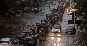 Commuters walk through water-logged roads after rains in Mumbai on Tuesday. Photograph: Shailesh Andrade/Reuters