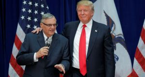 Donald Trump is joined onstage by former Maricopa county sheriff Joe Arpaio (Left) at a campaign rally in Marshalltown, Iowa in 2016, after Arpaio endorsed  Mr Trump's candidacy.