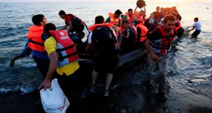 Migrants and refugees in a rubber dinghy arriving at Psalidi on Kos, Greece. Photograph: Jonathan Brady/PA Wire